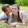 Teenage sister and little brother lying on hay — Stock Photo