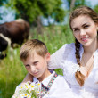 Teenage sister and little brother sitting by cow herd — Stock Photo #28386193