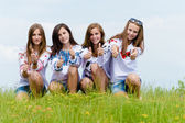 Four happy teenage friends showing thumbs up in green grass over blue sky — Stock Photo