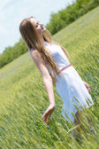 Young beautiful woman walking in green wheat field on summer day — Stock Photo