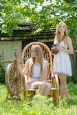 Two young women in country yard with spinning wheel and rock chair — Stock Photo