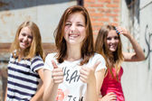 Three young happy teenage girls showing thumb up — Stock Photo