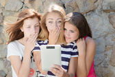 Three scared teen girl friends and tablet computer — Stock Photo