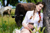 Young woman sitting tired near cows in countryside — Stock Photo