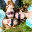 Three happy teen girls lying on green grass in sunglasses — Stock Photo