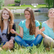 Three teen girls sitting in yoga position and meditating — Stock Photo #29235595