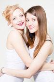 Dois amigos de mulheres felizes, abraçando e sorrindo em estúdio — Fotografia Stock