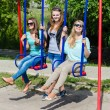 Three happy young women on swings — Stock Photo