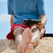 Young man sitting at seaside with tablet computer and resting — Stock Photo
