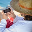 Man in hat in a hammock typing on touch phone screen on a summer day — Stock Photo
