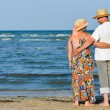 Happy mature couple resting at seashore and embracing — Stock Photo