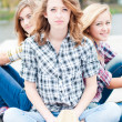 Three happy girls sitting together outdoors — Stock Photo #30447417