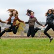friends girls jumping high in blue sky — Stok fotoğraf