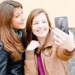 Two teen girls taking picture of themselves using tablet pc — Stock Photo