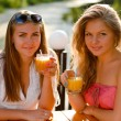 Two happy women drinking orange juice — Stock Photo #30449429