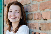 Young happy teenage girl standing at brick wall background copyspace — Stock Photo