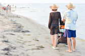 Young happy family with baby stroller walking on sandy beach — Stock Photo