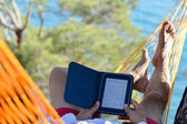 Man resting in hammock on seashore and reading ebook — Stok fotoğraf