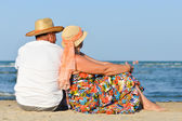 Happy mature couple sitting at seashore on sandy beach — Stock Photo