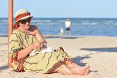 Happy mature woman sitting on beach and knitting — Stock Photo