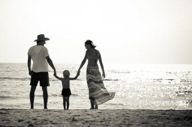 Happy family of three on sandy beach having fun