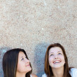 Two happy teen girls looking up on copy space — Stock Photo #31203357