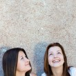 Two happy teen girls looking up on copy space — Stock Photo