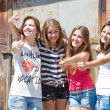 Four happy teen friends showing thumbs up outdoor on rusty wall background — Foto de Stock