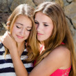 Teenage girl comforting crying friend with warm hug — Stock Photo