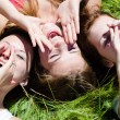 Three happy teen girls lying on green grass looking into sky and holding hands — Stock Photo #31204623