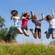 Four happy teen girls friends jumping high against blue sky — Stock Photo #31204969