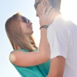 Young happy couple embracing against bright summer sky — Stock Photo #31206127