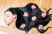 Haircare, young beautiful woman with long dark hair and flowers — Stock Photo
