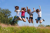 Four happy teen girls friends jumping high against blue sky — Stock Photo