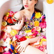 Beautiful sexy young female in bath with flowers and fruit — Stock Photo