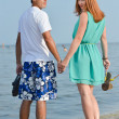 Young happy couple walking holding hands on seashore — Stock Photo