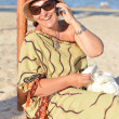 Happy mature woman sitting on beach and talking on mobile phone — Stock Photo