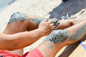 Man applying mineral blue mud on knee — Stock Photo