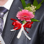 Beautiful gerbera boutonniere on groom suit — Stock Photo