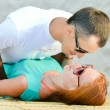 Young happy couple embracing on sandy beach — Stock Photo