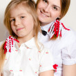 Two happy beautiful teenage and little sisters wearing white blouses — Stock Photo