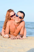 Young happy couple man and woman lying on sandy beach — Stock Photo