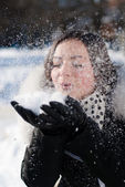 Beautiful young happy smiling woman blowing on snow flakes — Stock Photo