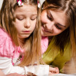 Elder sister teaches to read younger one — Stock Photo