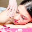 Beautiful woman relaxing during massage with flowers, perfect skin — Stock Photo