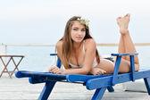 Young woman enjoying sunny day on sun lounge — Stock Photo