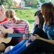 Stock Photo: Four happy teen friends playing guitar in green summer park