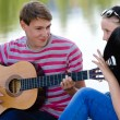 Three happy teen friends playing guitar in green summer park — ストック写真