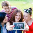 Stock Photo: Four happy teen friends taking picture of themselves with tablet
