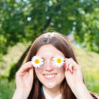 Funny teen girl holding daisy flowers at her eyes — Stock Photo